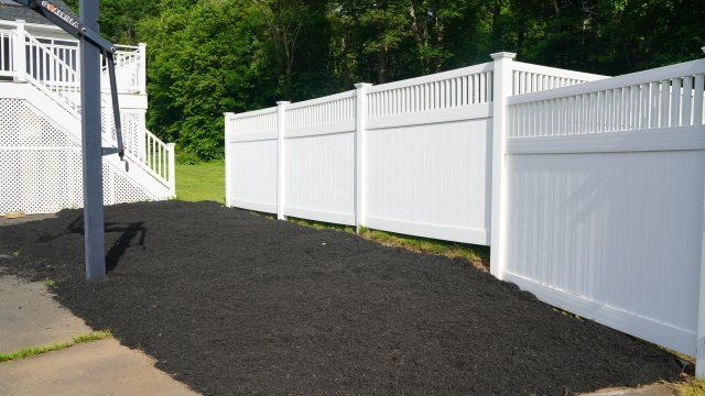 White fence bordering newly tarred ground